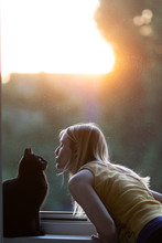 Black Cat And Woman In Front Of Window At Sunset