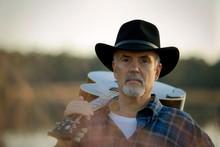 Portrait Of A Mature Man Holding An Acoustic Guitar Over His Shoulder.
