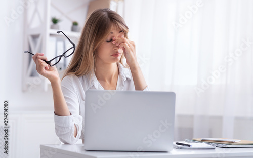 Obraz Overworked Girl Massaging Nosebridge Sitting At Laptop At Workplace - fototapety do salonu