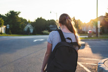 Teen Girl Depressed/sad At Sunset In A Parking Lot While Wearing A Backpack And Holding Binders.