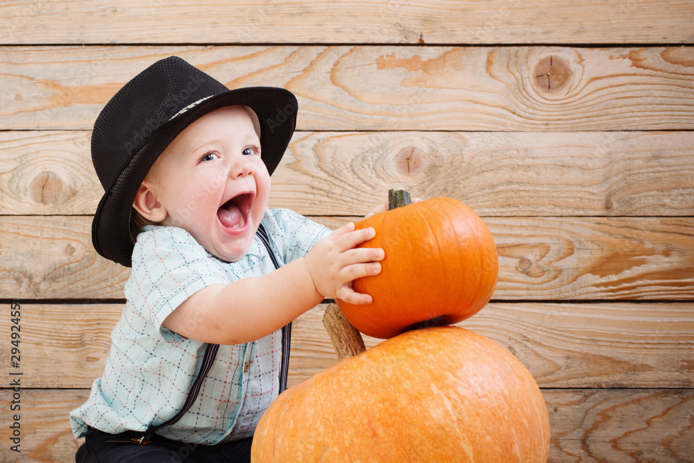 Fototapety, obrazy: baby in black hat with pumpkins on wooden background