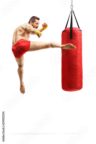 Man exercising kickbox and punching a bag with leg Canvas Print