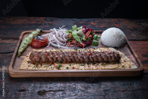 Photo Turkish lula lamb or beef kebab with rice and vegetables isolated on rustic wood