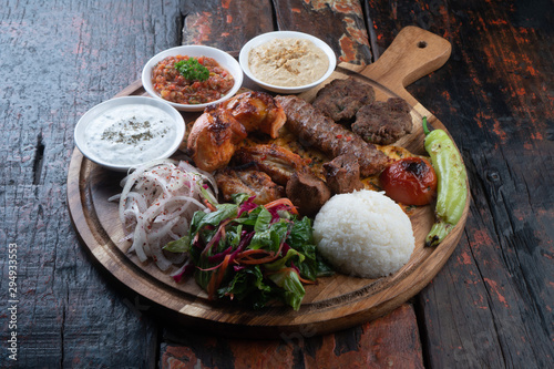 Canvas Print Mixed turkish kebab plate with rice, vegetables and dip sauces isolated on rusti