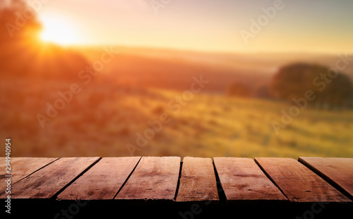 A wooden table top planks product display with a blurred background scene of farmland at sunset Fotobehang
