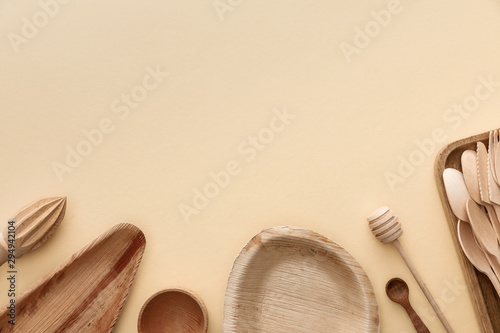 Pinturas sobre lienzo  top view of wooden plates, spoons and hand juicer on beige background