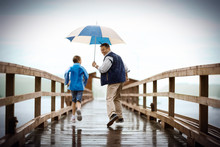 Man Holds An Umbrella Over His Young Daughter As They Laugh And Run Together Along A Jetty In The Rain.
