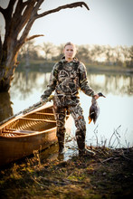 Portrait Of A Young Adult Woman Duck Shooting By A Lake.