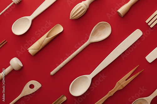 Cuadros en Lienzo top view of natural wooden spoons, fork and kitchenware on red background