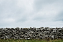 View Of Old Dry Stone Wall Under A Cloudy Sky.