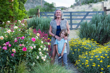 Smiling Grandmother And Grandson Standing In Garden