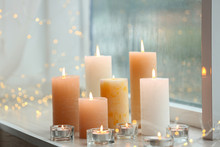 Beautiful Burning Candles And Fairy Lights At Windowsill On Rainy Day