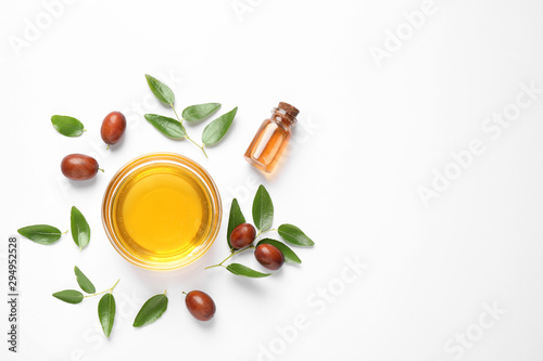 Fotografie, Obraz Bowl with jojoba oil and seeds on white background, top view