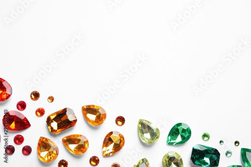 Fotografía  Different beautiful gemstones on white background, top view