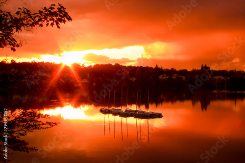 Montage in der Fensternische Rot Group of sailboats on a lake at sunset. Houses and forest in the background. Colored dramatic sky and clouds.