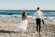 Rear View Of Bride And Groom Running On The Beach