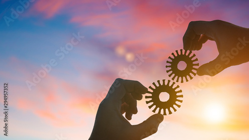 Fototapeta  Silhouette two businessmen hands collect old gears into a puzzle, on sunset background