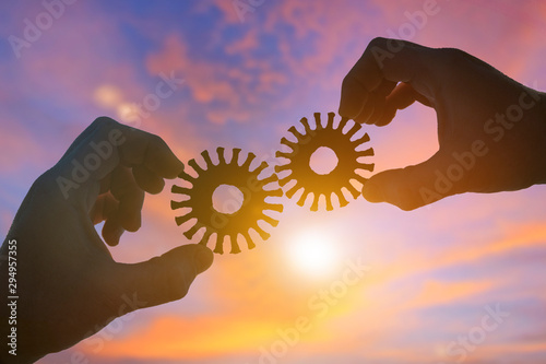 Fotografie, Obraz  Silhouette two businessmen hands collect old gears in posl, on sunset background