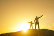 canvas print picture - Father with a baby girl on top of the mountain, raising his hands up, playing outdoors on a sunset background. Happy loving family