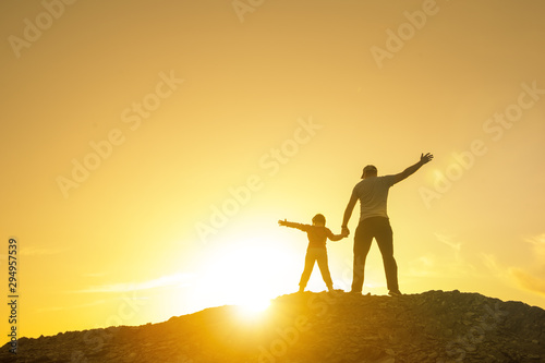Father with a baby girl on top of the mountain, raising his hands up, playing outdoors on a sunset background Canvas Print