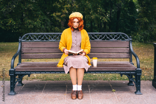 Photo A beautiful red-haired girl with a curly hairstyle is sitting on a park bench and reading a book