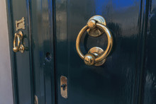 Teal Color Doors And Two Round Brass Door Knocker