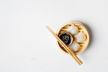 Traditional Chinese Steamed Dumplings Dim Sums In Bamboo Steamer With Sauces And Chopsticks On Light Surface With Copy Space. Asian Food Background.
