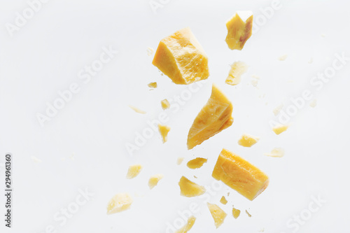 Fototapeta Parmesan cheese flying in different directions with crumbs on a white background with space for the text. obraz