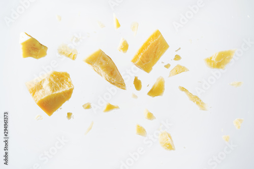 Leinwand Poster Parmesan cheese flying in different directions with crumbs on a white background with space for the text
