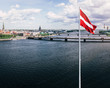 Panoramic view of Riga and Latvian flag in foreground.