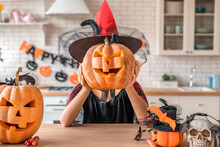 Beautiful Woman In Witch Costume With Pumpkins Near Her Head. Happy Halloween Concept!