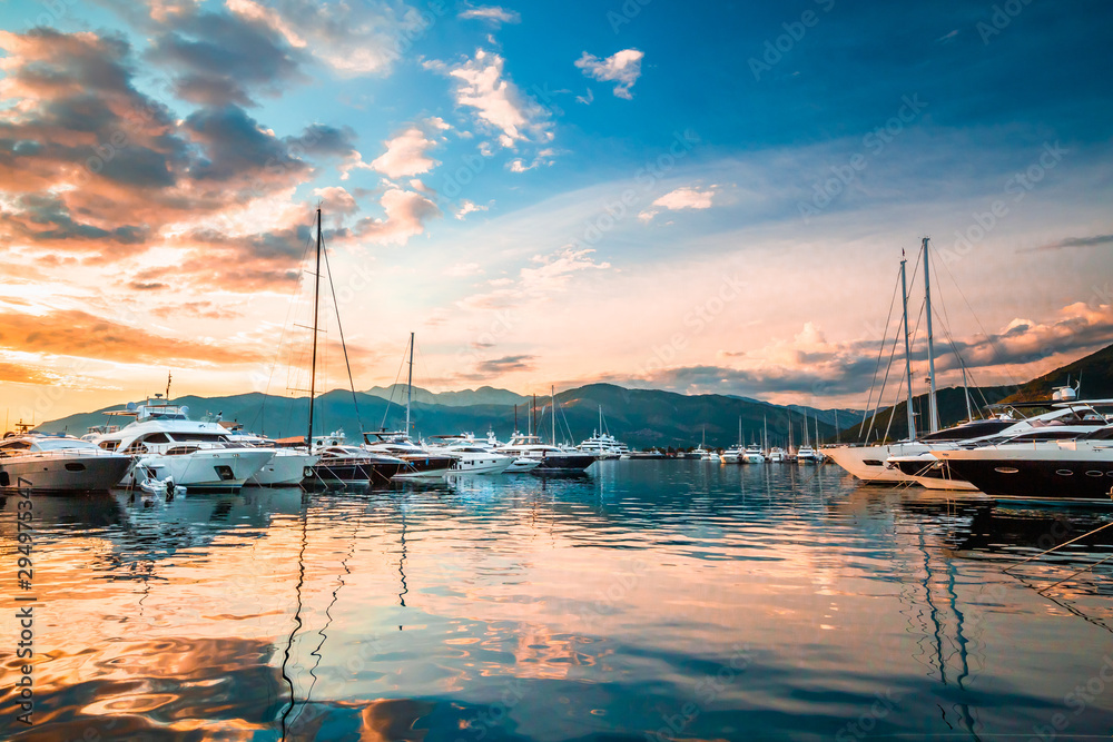 Fototapety, obrazy: Luxury yachts and motor boats docked in marina Porto Montenegro in Mediterranean sea at sunset.