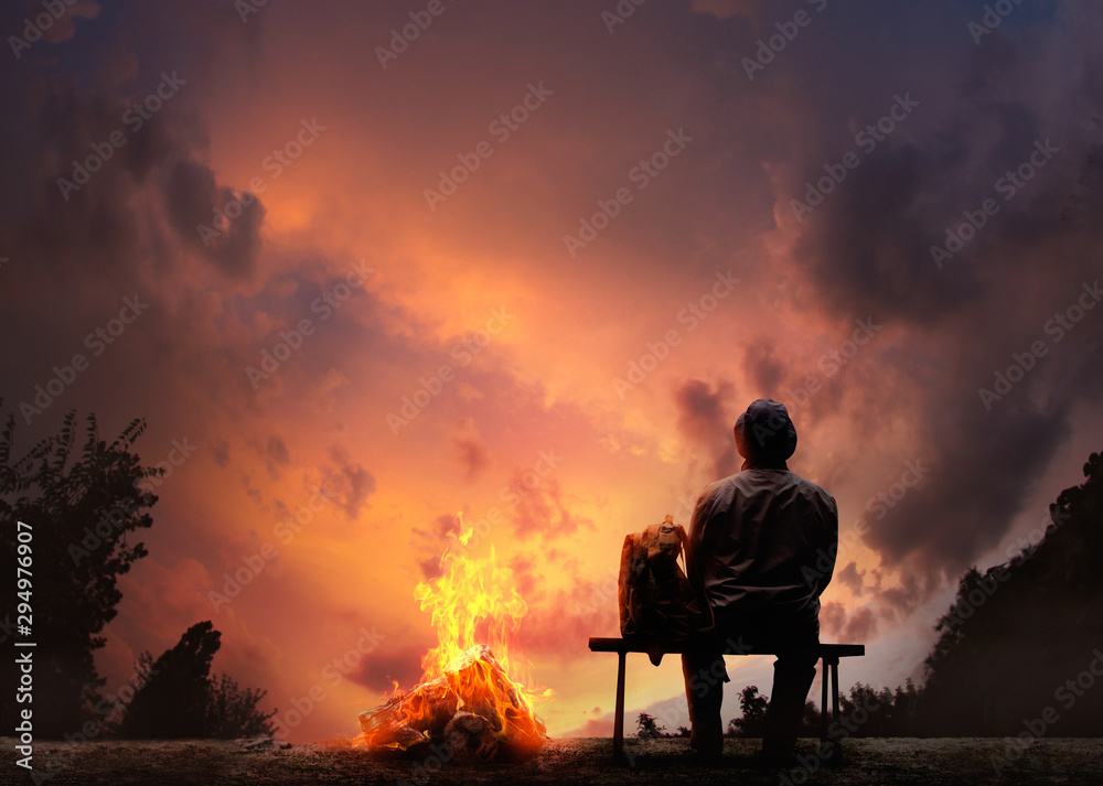 Fototapety, obrazy: Male traveller sitting on a bench near bonfire on sunset .