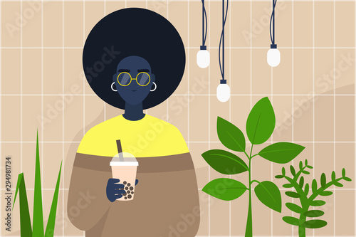 Young black female character holding a cup of boba bubble tea to take away in a Fototapet