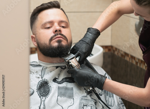 Stylist cutting males beaver with clipper, close up view. Masters hands in black rubber gloves. Interior of barbershop. Selective soft focus. Blurred background