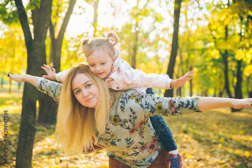 piggyback mother playing with daughter at autumn city park Fototapete