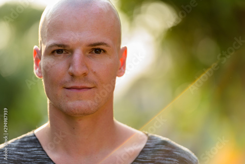 Fotomural  Close up of young handsome bald man outdoors