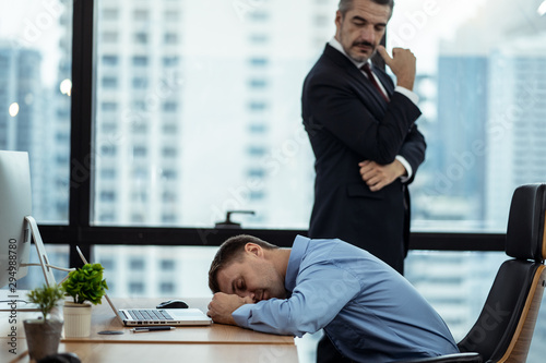 Working Caucasian man feeling drowsy and sleeping on desk in office due to overload job and fussy boss came behind looking at him feeling angry Poster Mural XXL