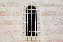 Window With Grate In The Brick Wall Of Church