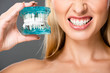 cropped view of naked woman showing teeth and holding jaw model isolated on grey