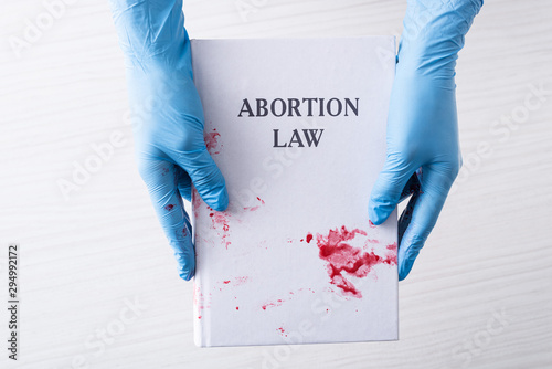 Photo cropped view of doctor in latex gloves holding book with abortion law letters