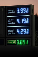 A Digital Gas Station Sign Displays Current Fuel Prices Next To A Road In The United States During The Evening.