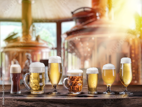 Fényképezés Beer glasses on wooden table and copper brewing cask at the background