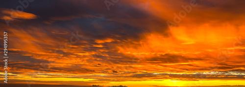 Foto auf Gartenposter Rotglühen Panorama Sunlight with dramatic sky. Cumulus sunset clouds with sun setting down on dark background.Vivid orange cloud sky.