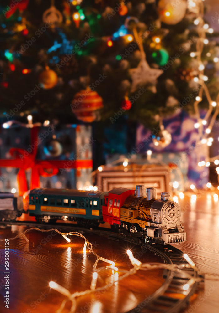 Fototapeta toy vintage steam locomotive on the floor under a decorated Christmas tree on a background of bokeh lights garland.
