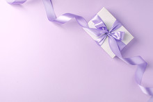 Craft Gift Box On A Lilac Background, Decorated With A Textured Bow And Feathers, Creating A Romantic Luxury Atmosphere. For Birthday, Anniversary Presents, Gift Post Cards.