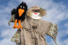Cute Humanoid Scarecrow Together With A Crow On A Background Of Blue Sky, Ukraine. Close Up