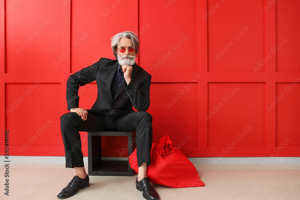 Fototapeta Portrait of stylish Santa Claus with bag indoors