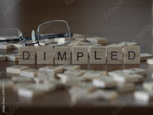 Valokuva  The concept of Dimpled represented by wooden letter tiles