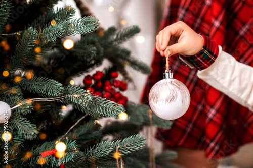 Fototapeta Little child's hand decorating Christmas tree indoors. obraz